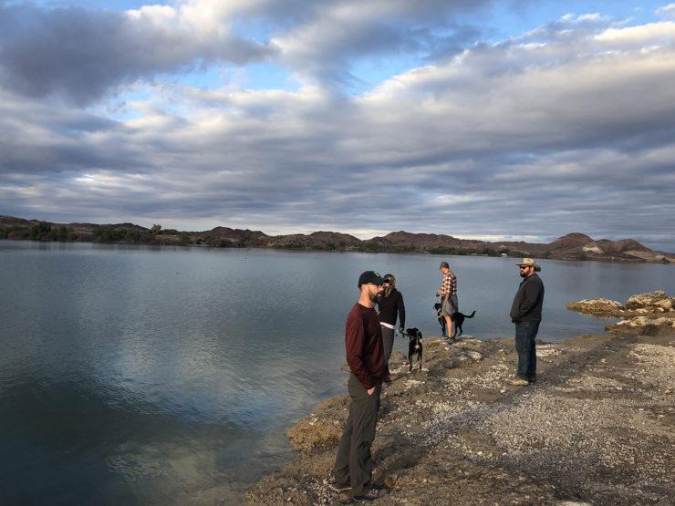 people standing next to lake